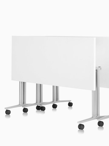 Three white Everywhere Tables, nestled together in the folded position. Select to go to the Everywhere Tables product page.