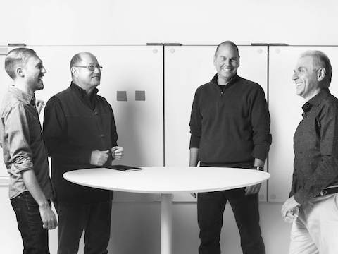 Four product designers from Continuum interact around a table.