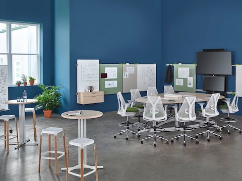Sayl office chairs surround a teardrop Exclave table in a collaboration space with a wall-hung media tile and display boards.