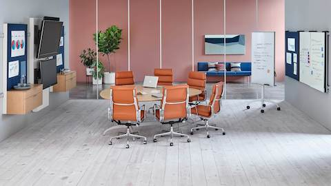 Six burnt-orange Eames Soft Pad Chairs surround a teardrop table in a collaboration space featuring Exclave display elements.