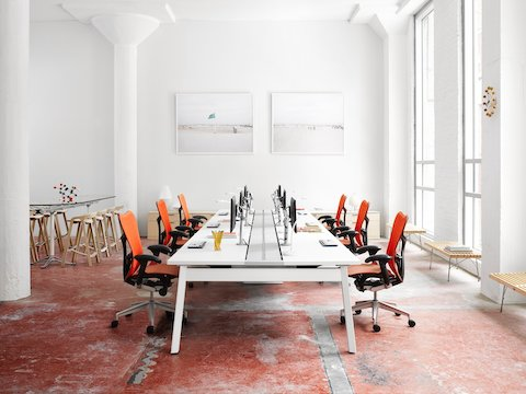 Orange Mirra 2 office chairs line either side of a Canvas Beam-based work surface with attached Flo Monitor Arms.