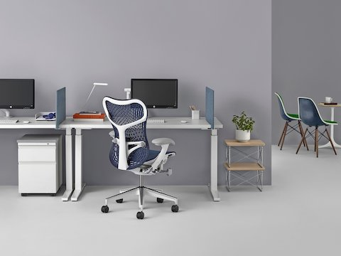 An individual work point featuring a blue Mirra 2 office chair, Renew Sit-to-Stand Table, and Flo Monitor Arm.