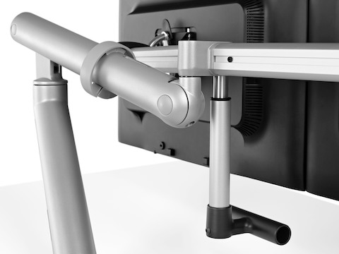 Close-up of an adjustable Flo Monitor Arm, showing its attachment to the rear of a computer monitor.