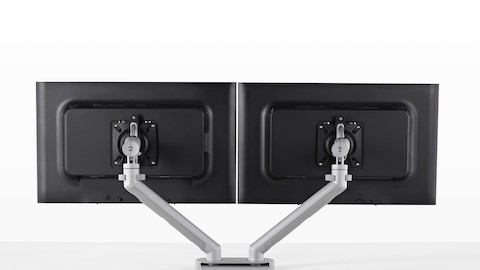 Rear view of two monitors attached to a Flo Modular Monitor Arm.Rear view of side-by-side monitors supported by a Flo Dual Monitor Arm that's attached to a desk.