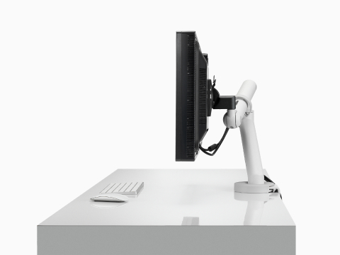 Profile view of a monitor supported by a heavy-duty Flo Plus Single Monitor Arm.