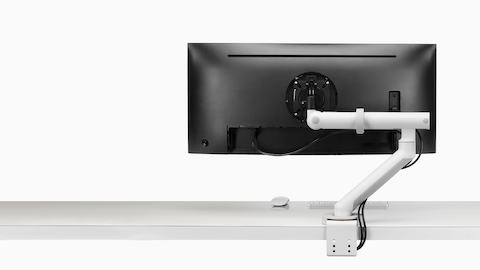 Profile view of a monitor supported by a heavy-duty Flo Plus Single Monitor Arm adjusted to a low position.