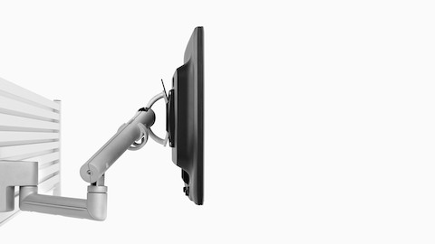 Profile view of a monitor supported by an adjustable Flo Rail Tile Mount attached to a panel-mounted rail system.