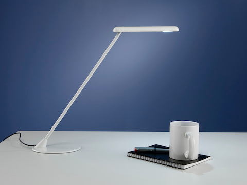 A white freestanding Flute Personal Light joins a notepad and coffee cup on a desktop.