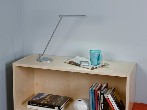 A silver freestanding Flute Personal Light, newspaper, and coffee cup atop a low bookcase.