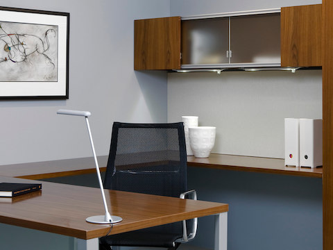 A white freestanding Flute Personal Light perched on the edge of a work surface in a private office.