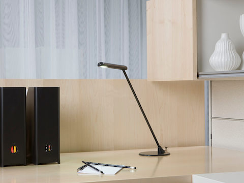 A black freestanding Flute Personal Light provides targeted illumination on a desktop.