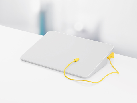 A white Formwork Media Stand and yellow charging cable.