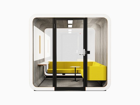 A white Framery 2Q Office pod with a yellow sofa, small table, and marker board.