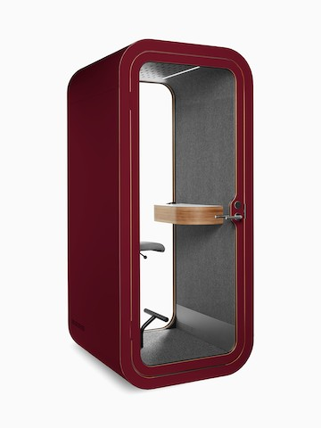 A maroon Framery O Office Phone Booth with a gray fabric interior, small shelf, and stool.