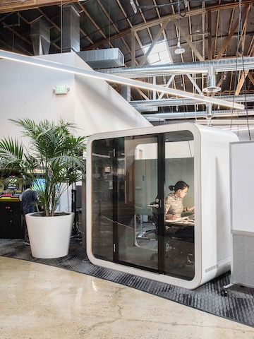 A white Framery Q Office Pod in an open office setting with a woman working inside.