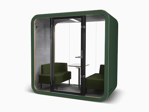 A green Framery Q Meeting Pod with a small table, power access, and sofas.