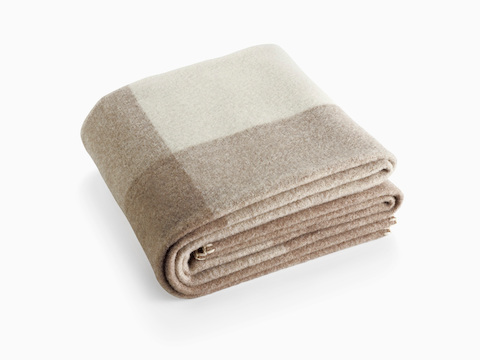 A folded Girard Throw blanket in shades of beige and ivory.