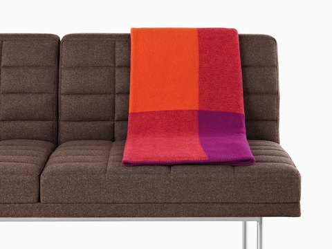 A Girard Throw blanket in shades of orange and magenta folded over the back of a brown Tuxedo Sofa.