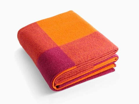A folded Girard Throw blanket in shades of orange and magenta.