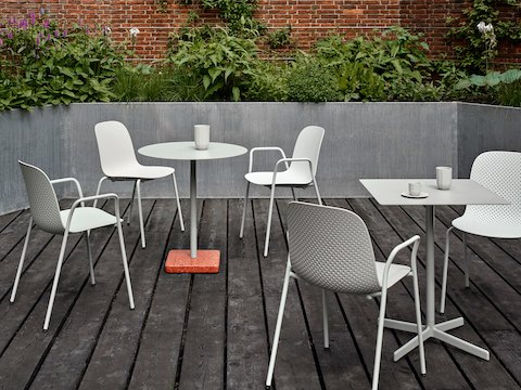 Exterior patio setting with white 13Eighty Chairs and Terrazzo Tables.