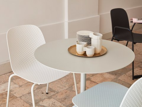 A close-up view of two white 13Eighty Chairs placed at a white Terrazzo Table.