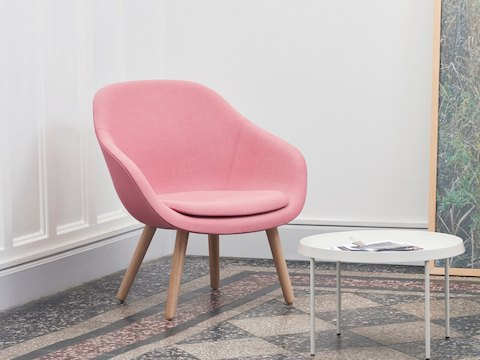 A pink About A Lounge Chairs with a wooden base, and a Tulou Coffee Table in white.
