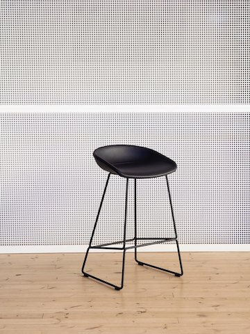 Black About A Stool, standing against wall alone, viewed at an angle.