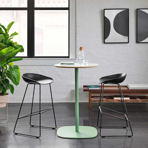 Two all black About A Stools stationed at a naughtone Ped Bar Height Table with a white top and green base.
