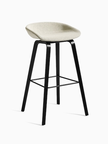 Off-white upholstered About A Stool with black wooden base, viewed at an angle.