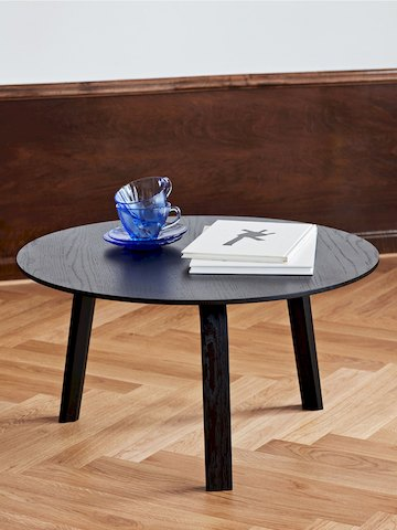 Black Bella Coffee Table standing alone, holding books and dishes.