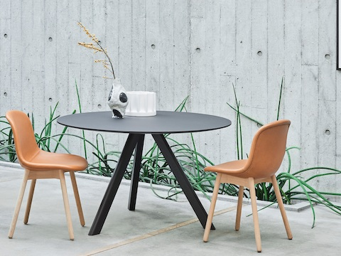 Round, black Copenhague Table located outside with two tan About A Chairs.