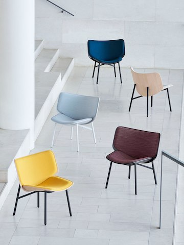 Five Dapper Lounge Chairs of varying colors and orientations, arranged on the large landing of a grand stairwell.