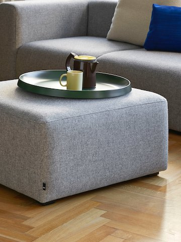 A gray Mags Ottoman, viewed at an angle in front of a gray Mags Sectional Sofa.