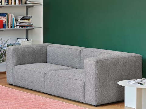 gray, 2-piece Mags Sectional Sofa with white, round Slit Table in a living room.