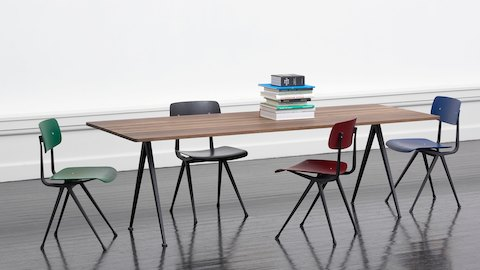 Green, black, red, and blue Result Chairs with black frames, placed around a smoked-oak Pyramid Table.