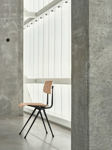 Oak Result Chair with black frame, standing alone between two cement pillars, viewed at an angle.
