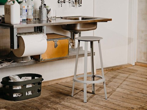 gray Revolver Stool placed in front of a sink in a work room.