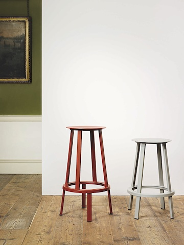 Red and gray Revolver Stools with two different heights standing next to eachother against a wall.
