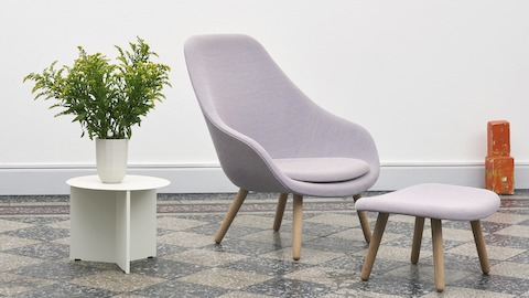 White, round Slit Table alongside purple About A Lounge Chair and Ottoman.