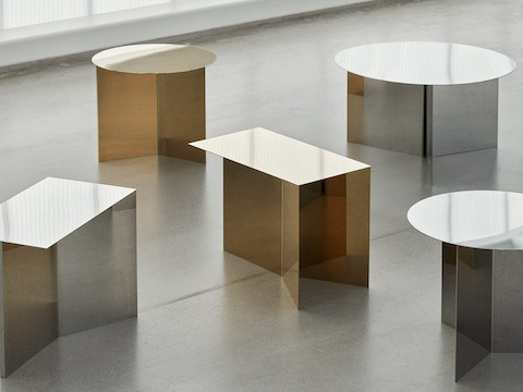 An oblong, round, and hexagon Slit Table in mirror, green, and black are staged together.