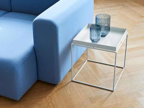 White, square Tray Side Table alongside light blue Mags Sectional Sofa.