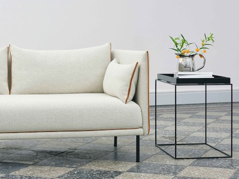 Black, square Tray Side Table alongside off-white Silhouette Sofa.