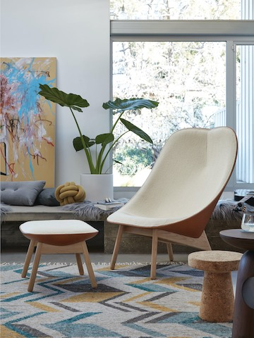 A cream Uchiwa Lounge Chair and Uchiwa Ottoman in a living area with a house plant and artwork.