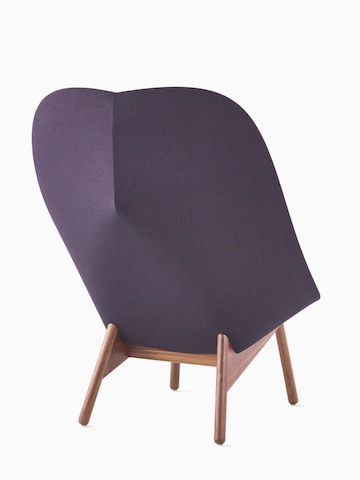 A purple Uchiwa Lounge Chair from HAY, viewed from behind to display the wrap of the upholstery around its curved form.