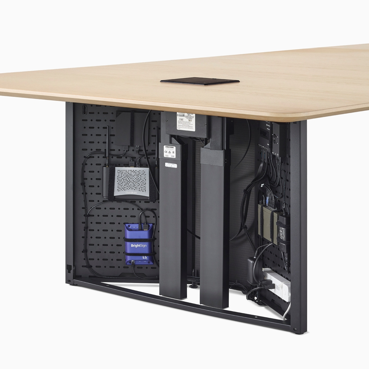 A close-up view of a Headway conference table's open cabinet base filled with technology components.