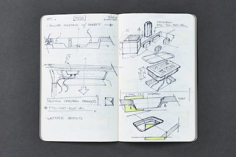 A close-up view of a notebook containing sketches of prototypes for Headway conference table's design.