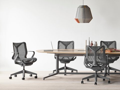 An office setting featuring a Headway conference table with a Y base surrounded by seven Cosm office chairs.