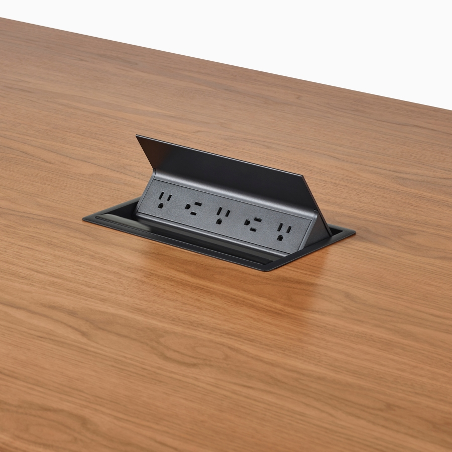 A close-up view of Logic power access installed in the surface of a Headway conference table.