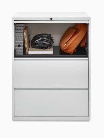 Personal items occupy the top shelf of a three-high storage unit with tambour doors, part of Herman Miller's Global Storage System.