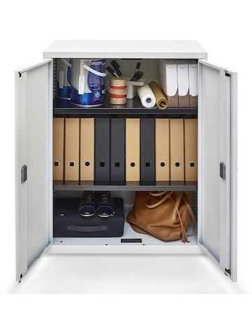 Open hinged doors on a Value storage cupboard reveal binders and personal items inside.
